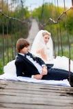 Novio de la novia que se sienta en el puente imágenes de archivo libres de regalías