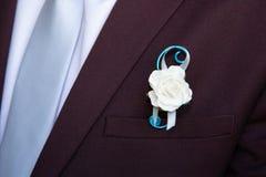 Novio del detalle que lleva el ramillete floral de la chaqueta de la decoración de los pernos imagen de archivo libre de regalías