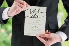 Novio en el traje negro que celebra casarse la invitación imagenes de archivo