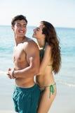 Novio feliz de abarcamiento de la mujer en la playa Imagenes de archivo