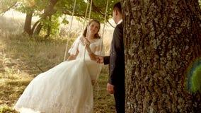 Novio feliz que balancea en un oscilación a la novia en el parque en verano oscilación del muchacho y de la muchacha en una ram almacen de metraje de vídeo