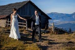 Novio feliz y novia que caminan en el campo de la montaña honeymoon imágenes de archivo libres de regalías