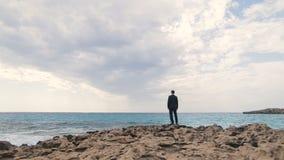 Novio hermoso elegante que se coloca solamente en la playa rocosa y que mira en el mar chipre metrajes