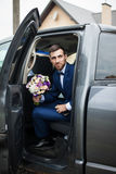 Novio hermoso feliz con una barba, el salir del coche de la boda Imagenes de archivo