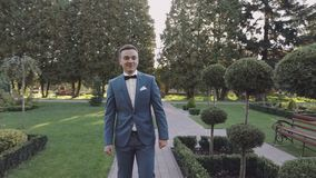 Novio hermoso que camina a través del parque Hombre bien arreglado Día de boda Cámara lenta almacen de video