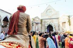 Novio indio que libra el caballo blanco al lugar de la ceremonia de boda con las huéspedes en Bangkok, Tailandia foto de archivo
