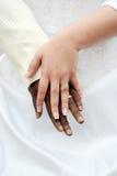 Novio negro y manos blancas del prometido con los anillos Fotos de archivo libres de regalías