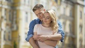 Novio que abraza a la novia suavemente, gente joven en el amor, relación romántica almacen de video