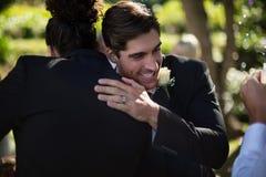 Novio que abraza a su amigo en parque Imagen de archivo