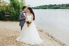 Novio que besa a la novia en la orilla del río Fotos de archivo