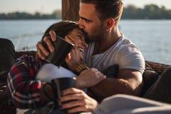 Novio que besa a su novia sonriente en frente por el rive foto de archivo