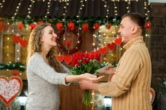 Novio que da las flores a su novia el día del ` s de la tarjeta del día de San Valentín Fotos de archivo