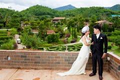 Novio que detiene a la novia asiática y feliz fotografía de archivo libre de regalías