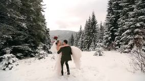Novio que hace girar a la novia feliz que la detiene y que hace girar en sus manos en bosque de la picea del árbol de abeto del t almacen de metraje de vídeo