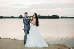 Novio que lleva a cabo las manos de la novia en la orilla del río Foto de archivo