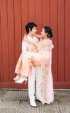 Novio tailandés Carrying Cute Bride en felicidad Fotos de archivo