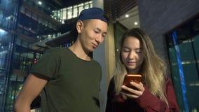Novio y novia asiáticos jovenes felices de los pares utilice un smartphone mientras que se coloca en una calle de la ciudad en la almacen de video