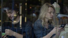 Novio y novia distante del trastorno que juegan en el smartphone que tiene problemas y dificultades de la relación almacen de video