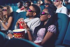 Novio y novia en los vidrios 3d que miran película en cine Foto de archivo libre de regalías