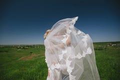 Novio y novia en un velo que coloca y que lleva a cabo las manos en la naturaleza en un fondo del cielo azul Fotografía de archivo