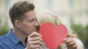 Novio y novia que abrazan y que ocultan detrás del corazón de papel, amor romántico almacen de metraje de vídeo