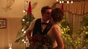 Novio y novia que intercambian los anillos de bodas en ceremonia del weddin del compromiso por las guirnaldas del bulbo y la deco almacen de video