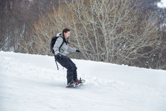 Novisflickan lär att skida med snowboarden Arkivfoto