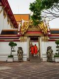 Novismunkarna som skriver in sidoingången av Wat Pho Temple i Bangkok royaltyfria bilder