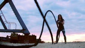 Novo, atlético, mulher, executa exercícios da força com a ajuda de uma corda grossa, desportiva No alvorecer, na pedreira arenosa filme