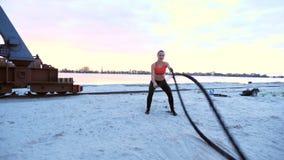 Novo, atlético, mulher, executa exercícios da força com a ajuda de uma corda grossa, desportiva No alvorecer, na pedreira arenosa video estoque