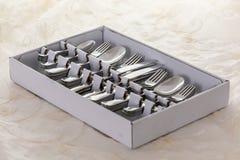 Novo da loja, das colheres, das forquilhas, das facas, das forquilhas do bolo e das colheres de chá em uma caixa, na tabela com t Imagem de Stock Royalty Free