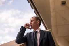 Novo e bem sucedido Homem de negócios novo considerável que olha ausente ao andar fora com prédio de escritórios no fundo Foto de Stock Royalty Free