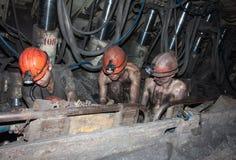 Novogrodovka, Ucrania - 18 de enero de 2013: Los mineros están ocupados el reparar del equipo del trabajo Imagen de archivo libre de regalías