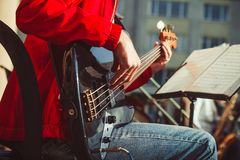 Novokuzneck, Russia - 13.08.2017: the bass guitarist plays in an orchestra on the street royalty free stock photo
