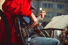 Novokuzneck Ryssland - 13 08 2017: de bas- gitarristlekarna i en orkester på gatan Fotografering för Bildbyråer