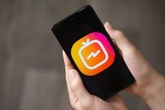 NOVOKUZNETS ROSJA, Czerwiec, - 24, 2018: Kobieta trzyma telefon z Instagram IGTV logem Zdjęcie Stock