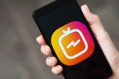 NOVOKUZNETS ROSJA, Czerwiec, - 24, 2018: Kobieta trzyma telefon z Instagram IGTV logem Fotografia Stock