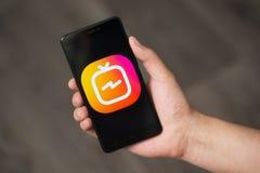 NOVOKUZNETS, RUSSIE - 24 juin 2018 : Équipez tenir un téléphone avec le logo d'Instagram IGTV Image stock