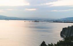 Novorossijsk, Russia, il 22 agosto 2015 Le imbarcazioni di mare nella baia alla luce di sera, osservano la città e la porta Fotografia Stock