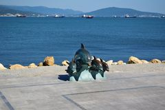 Novorossiysk, Rusland - Juli 3, 2018: Het bronsbeeldhouwwerk van dolfijnen bij de dijk stock fotografie