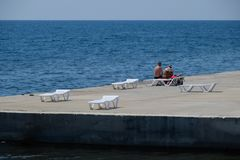 Chaise lounge is white on a stony beach by the coastline. Chaise lounge by the sea. Novorossiysk, Russia - August 06, 2018: Chaise lounge is white on a stony stock photo