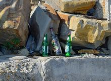 Empty bottles of alcohol. People left garbage. The beach of Novorossiysk. royalty free stock image