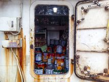 Warehouse with paint and household tools. The porthole of the porthole in the ship`s cabin Stock Photography