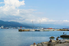 NOVOROSSIYSK, RUSSIA - MAY 08.2016: pier with yachts and the fishermen on the shore of the Black sea, Novorossiysk Royalty Free Stock Images