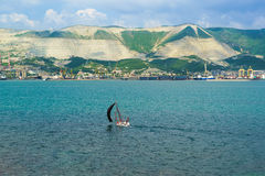 NOVOROSSIYSK, RUSSIA - MAY 08.2016: Sports sailboat and panorama of Novorossiysk commercial sea port Royalty Free Stock Photography