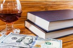 Novos livros, dólares e um vidro do vinho tinto em um fundo de madeira imagens de stock royalty free