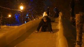 NOVOSIBIRSK, ΡΩΣΙΑ - 30 Δεκεμβρίου 2016: Τα παιδιά έχουν τη διασκέδαση στη φωτογραφική διαφάνεια πάγου κάτω από το λόφο το βράδυ φιλμ μικρού μήκους