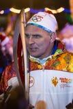 Novosibirsk, Rússia - 7 de dezembro: A entrevista dá Karelin Alexander com a tocha olímpica no relé de tocha olímpico Fotografia de Stock Royalty Free