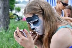 NOVOSIBIRSK ROSJA, CZERWIEC, - 26, 2016: Dziewczyna rysuje farby na jego twarz kagana zwierzęciu domowym Obrazy Stock