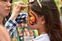 NOVOSIBIRSK ROSJA, CZERWIEC, - 26, 2016: Mistrz rysuje farba wzory na dziewczyny twarzy w miasto parku Obrazy Royalty Free